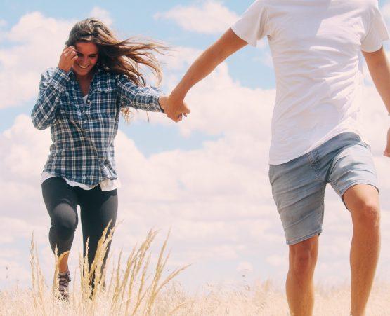 Una pareja que goza de salud y bienestar caminando por el campo.